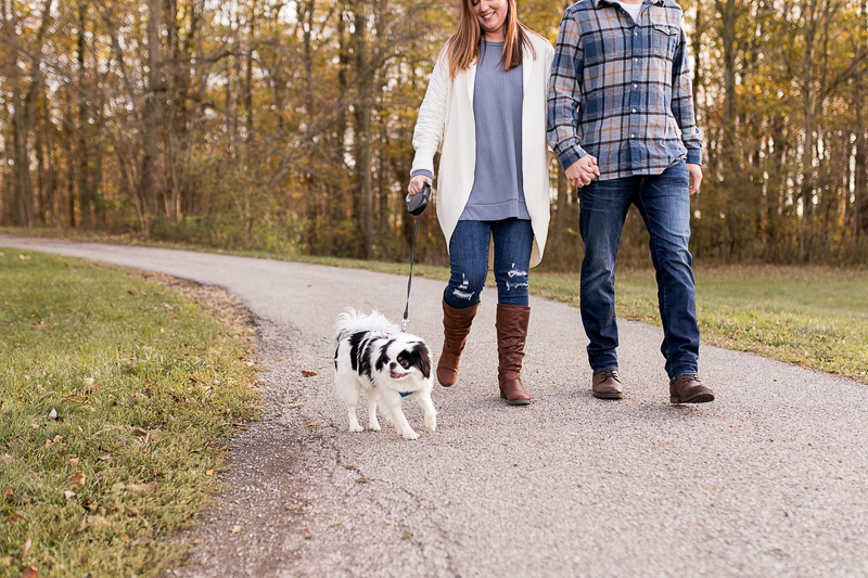 couple holding hands and walking their small dog, ©Autumn Howell Photography | dog-friendly engagement session, Kokomo, Indiana