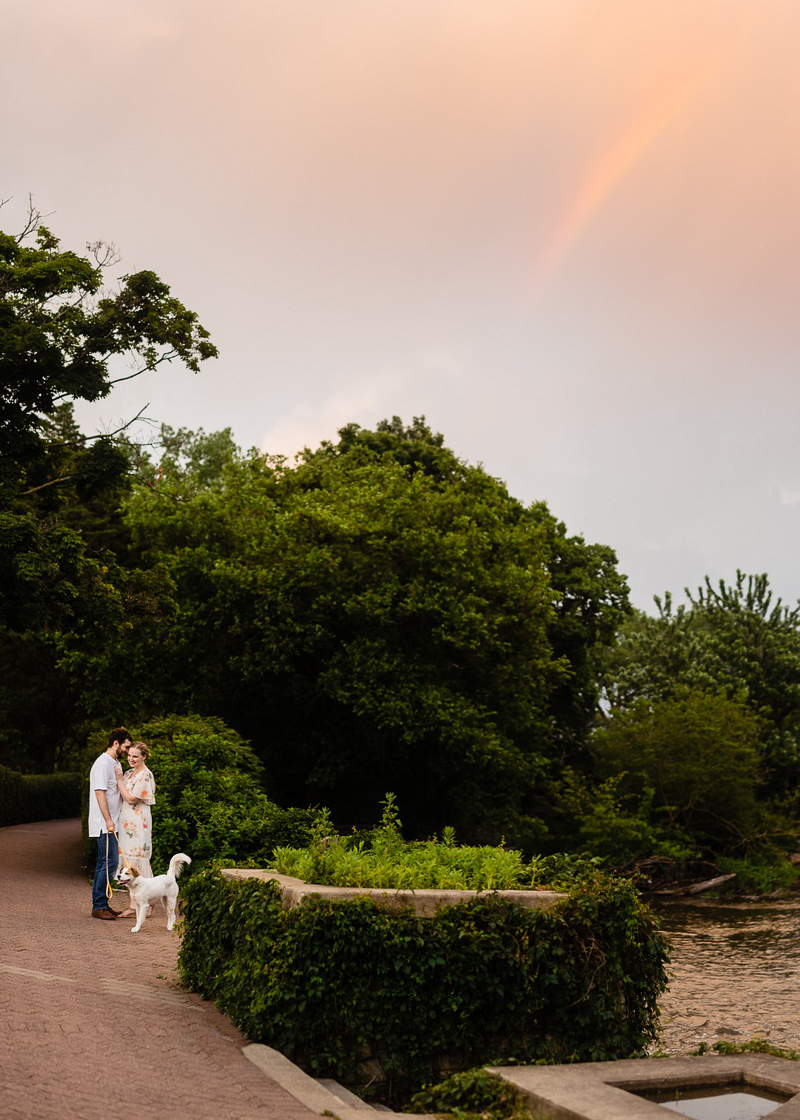couple an d pup on brick path by river, rainbow, golden hour engagement session | ©Jennifer Lourie, Naperville, Illinois
