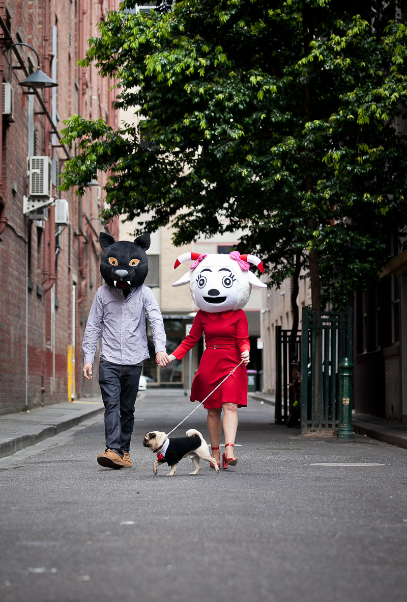 couple wearing big animal heads walking their dog, quirky engagement photos | ©Pupparazzi Pet Photography