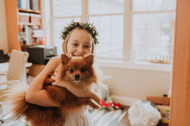 Pet-friendly first communion session, girl holding Pomeranian | ©Gardenhouse FIlms