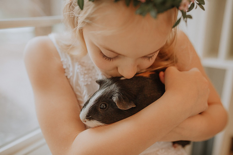 girl kissing her guinea pig, ©Gardenhouse FIlms | pet-friendly first communion session, Albany, NY