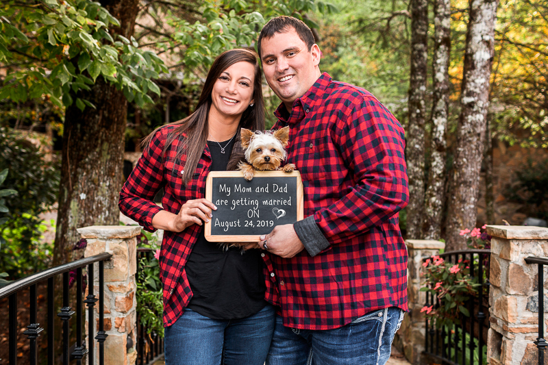 couple wearing buffalo plaid shirts, holding save the date sign with Yorkie | ©Cariad Photography | dog-friendly engagement session, Clayton, GA