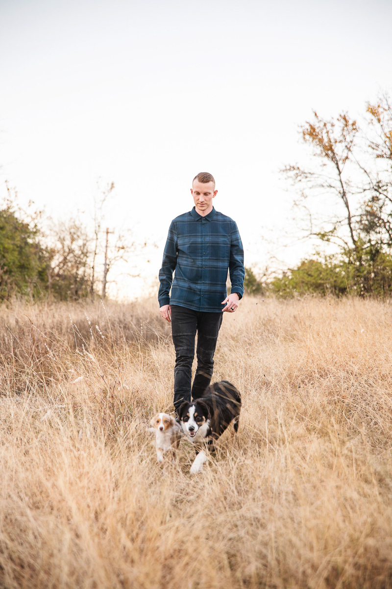 man walking through field with dogs, ©Monika Normand Photography | Dallas lifestyle dog-friendly family photography