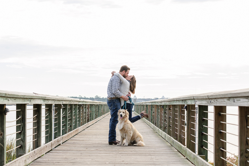 couple kissing on pier while dog sits in front of them | ©Charleston Photo Art, LLC, |