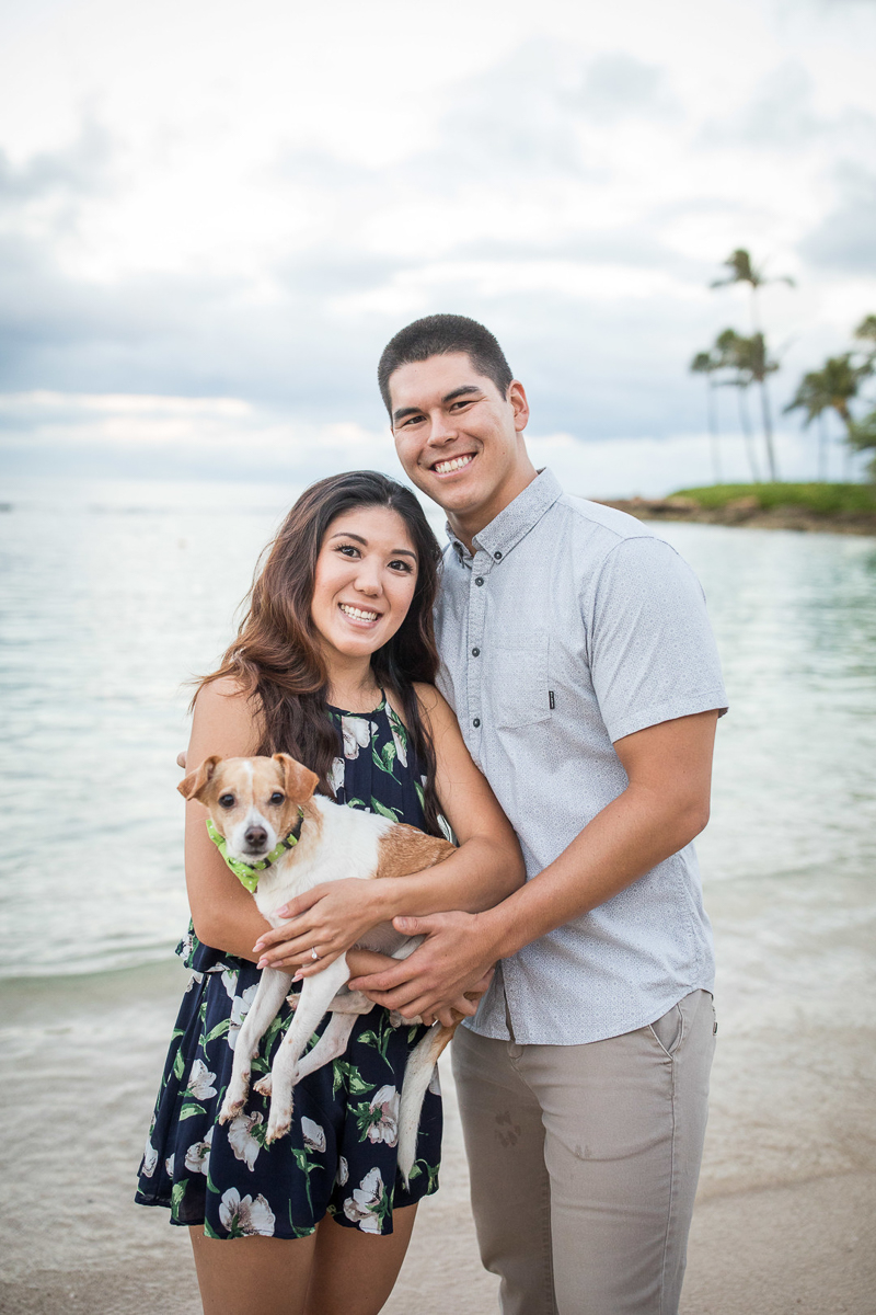 happy couple holding their small dog at water's edge | VIVIDfotos Hawaii engagement and wedding photography