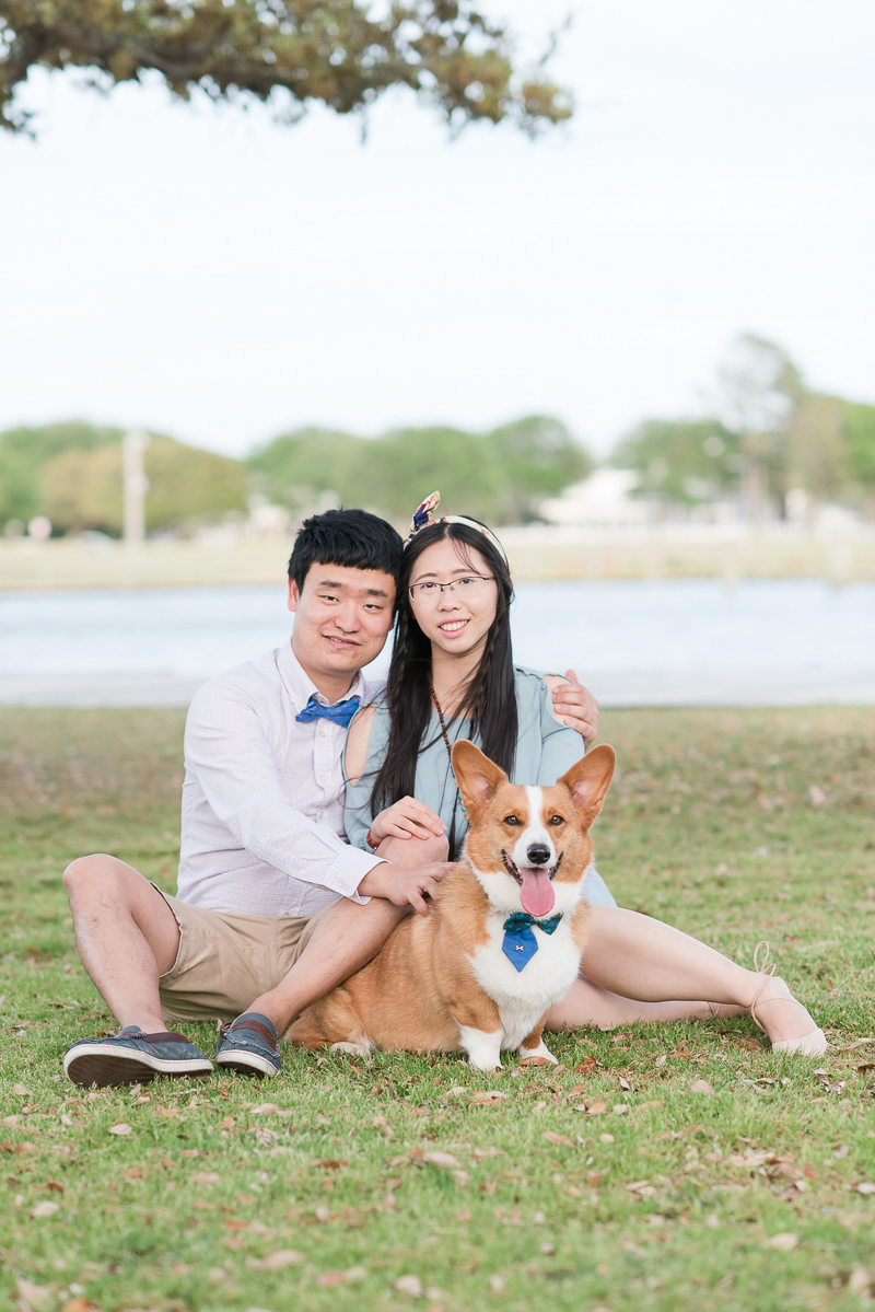 cute couple and their Corgi sitting on grass, Outer Banks photography session | ©Michelle & Sara Photography