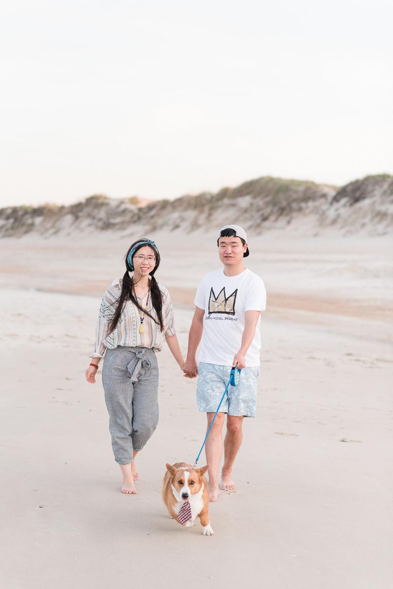 couple walking their Corgi on the beach | ©Michelle & Sara Photography