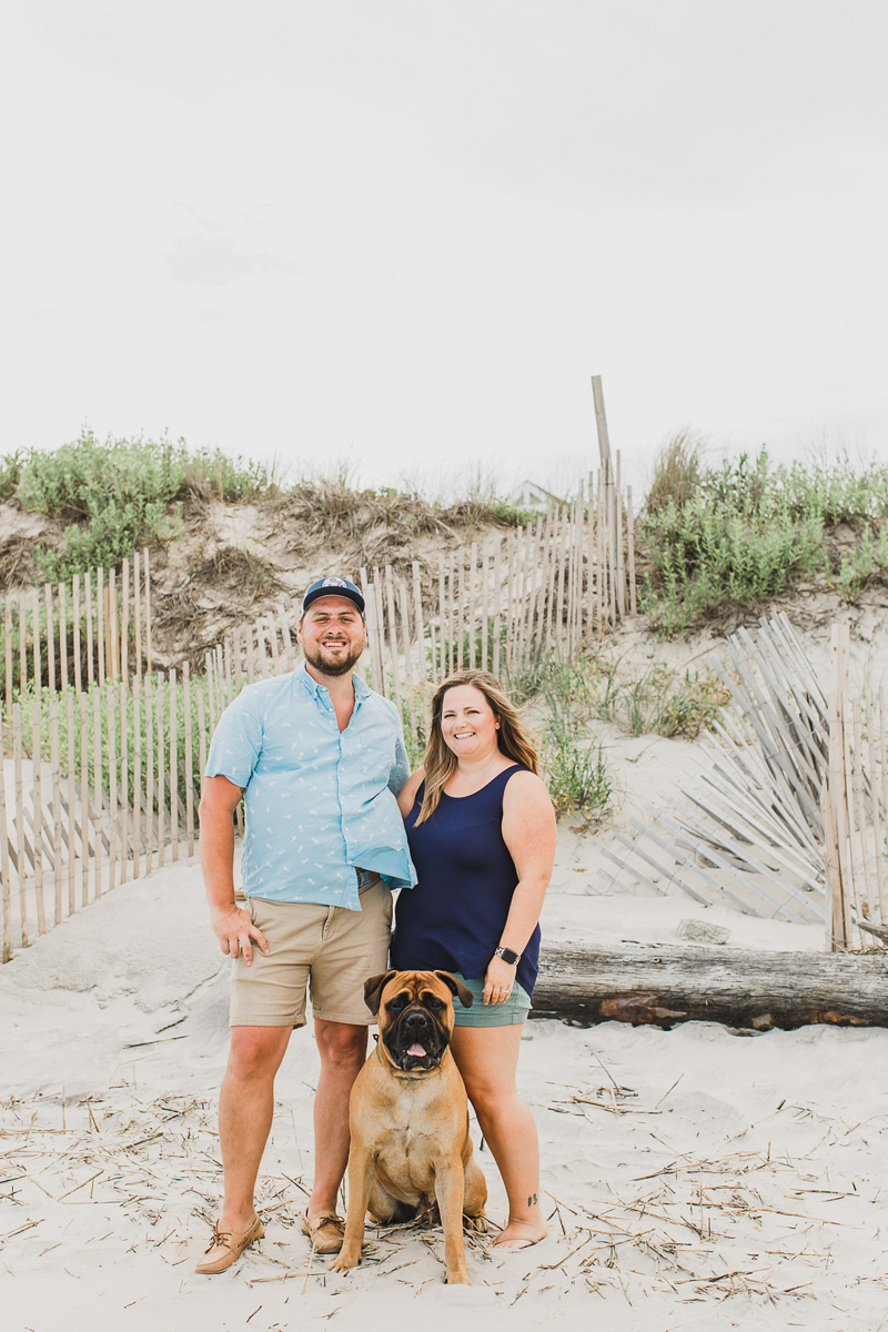 Bullmastiff and family in front of sand dune, dog-friendly family photos at the beach, Corolla, NC | ©Arli Quinn Photography
