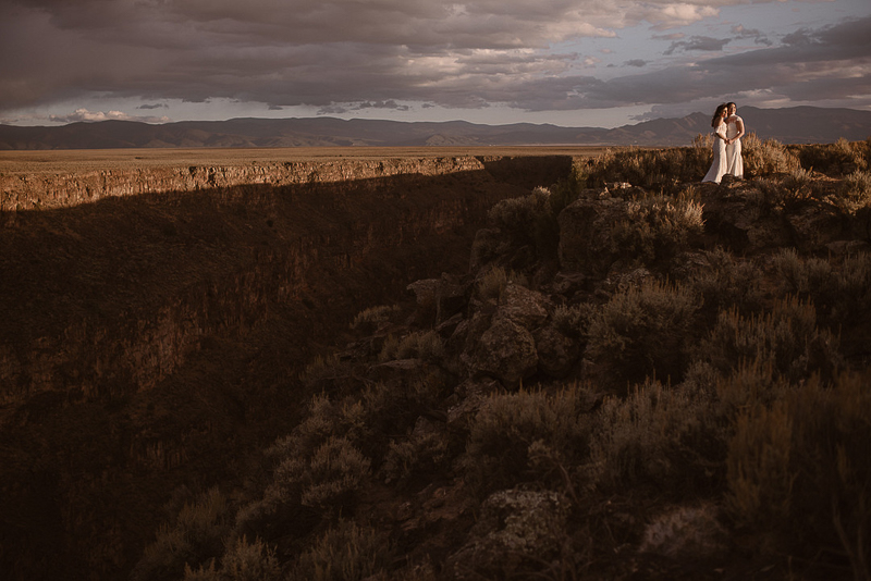 two brides watching sunset at Rio Grande Gorge, NM | ©Adventure Instead Elopement Photography