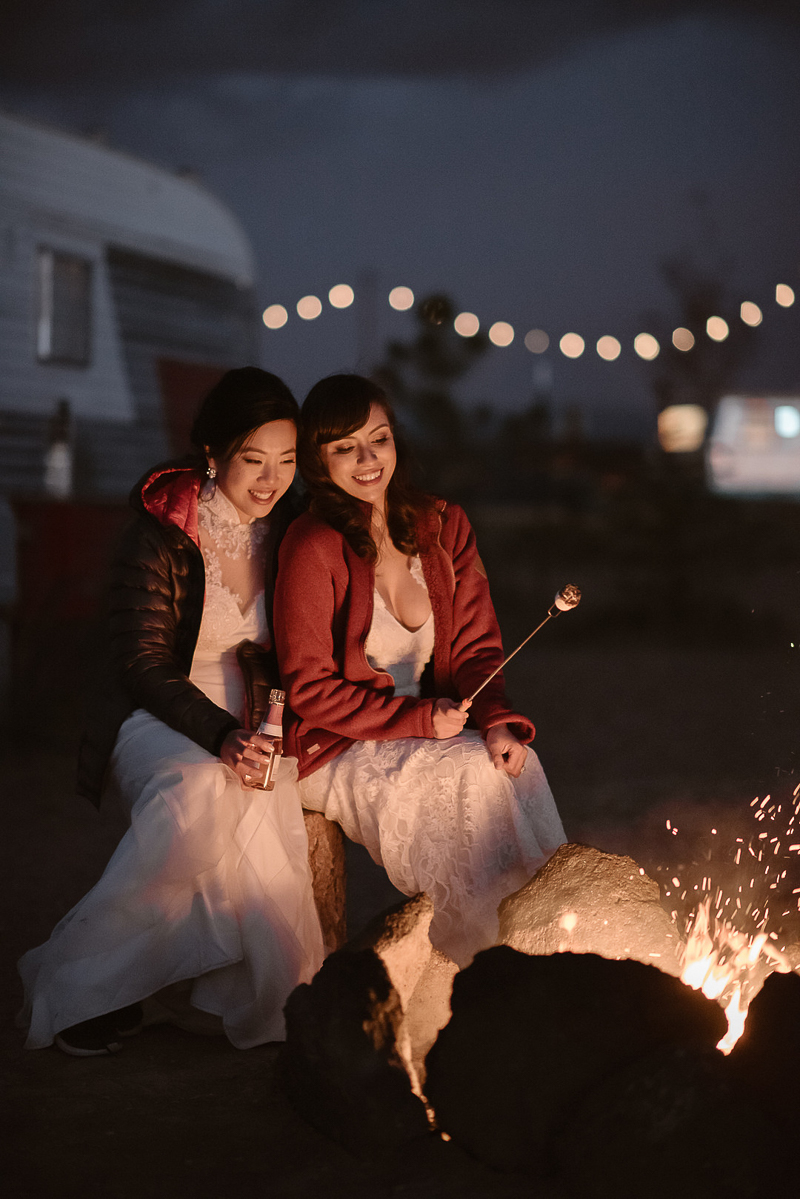brides roasting marshmallow around a fire, ©Adventure Instead Elopement Photography, Taos, NM