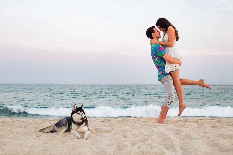 mini Husky lying on the beach, humans embracing | ©Fabi Rosas Photography, dog-friendly engagement session Cabo, Mexico