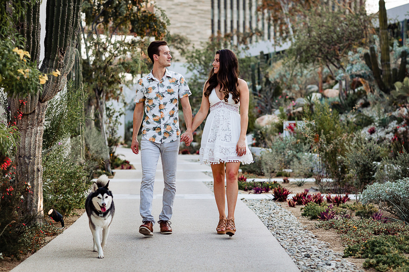 couple holding hands walking with their dog, Alaskan Klee Kai | ©Fabi Rosas Photography, dog-friendly engagement session Cabo, Mexico