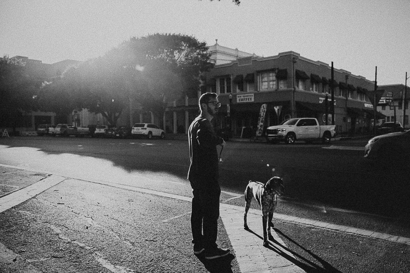 man and his dog in quaint downtown area | ©Joshua and Parisa | Austin Wedding Photographer and Videographer
