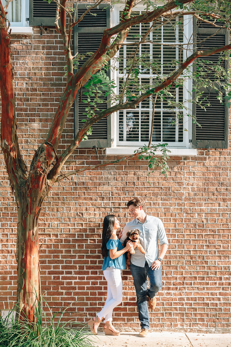 couple holding small dog and leaning against brick building, dog-friendly engagement poses, ©Charleston Photo Art