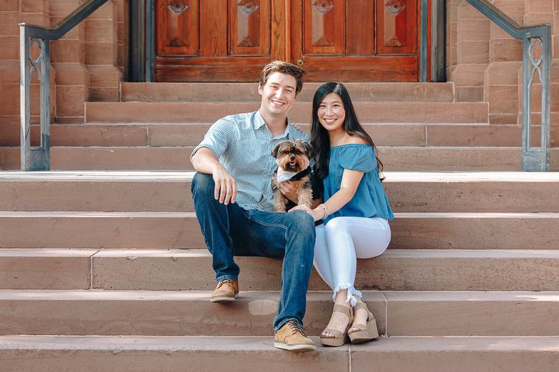 couple sitting on steps with Yorkie, dog-friendly engagement photos | ©Charleston Photo Art
