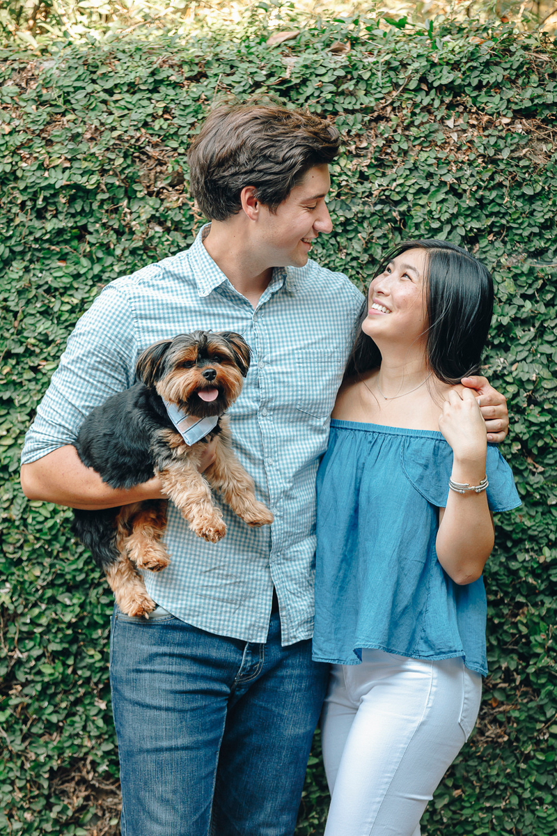couple standing in front of green hedge and holding Yorkshire Terrier, dog-friendly engagement ideas | ©Charleston Photo Art