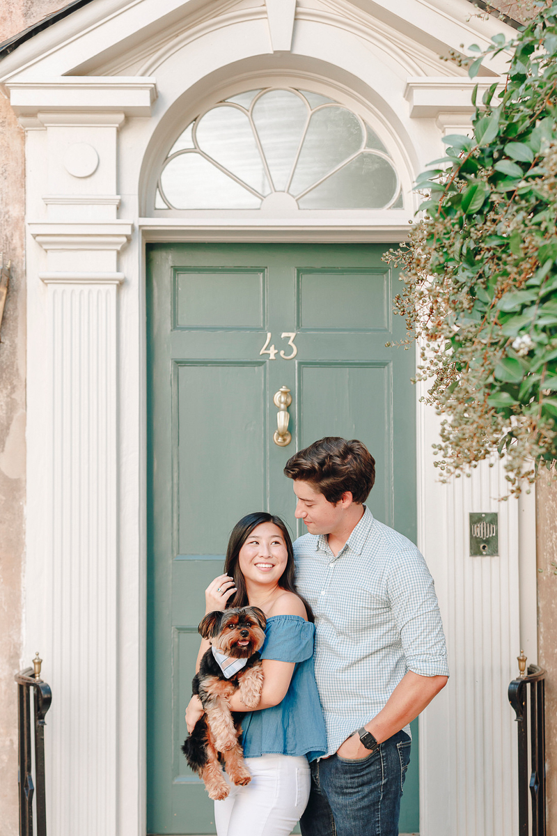 couple and their dog in front of sage green door, ©Charleston Photo Art   Legare Street Engagement Session