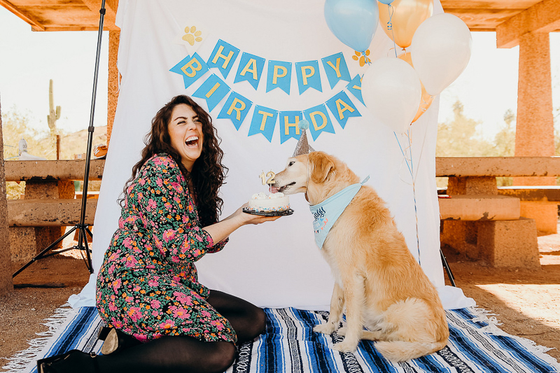 woman holding birthday cake for her dog, dog party ideas | ©Ali Tso Photography
