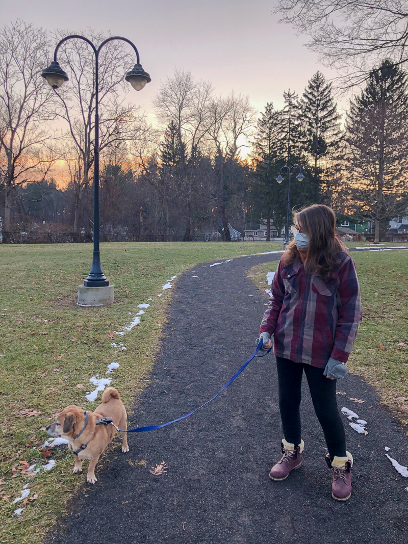 young woman walking the dog and wearing a mask, staying healthy during COVID-19 pandemic