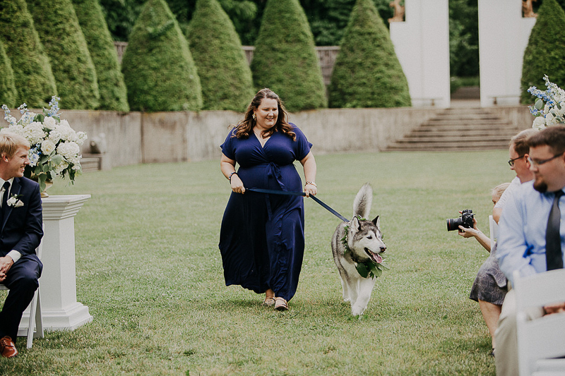 woman in navy dress walking dog in wedding, ideas to include dogs in weddings | ©McKenzie Bigliazzi Photography