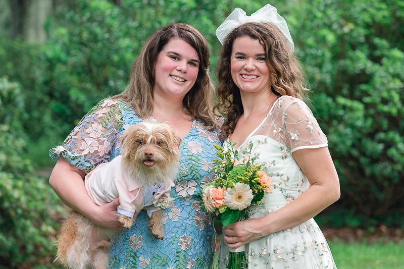 bridesmaid holding small dog, bride holding bouquet, small wedding | ©Charleston Photo Art