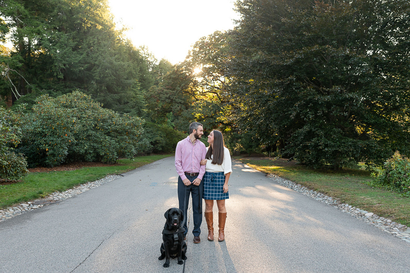 couple standing in the road, dog sitting in front of them, dog-friendly engagement ideas | ©Jess Sinatra Photography | Boston, MA
