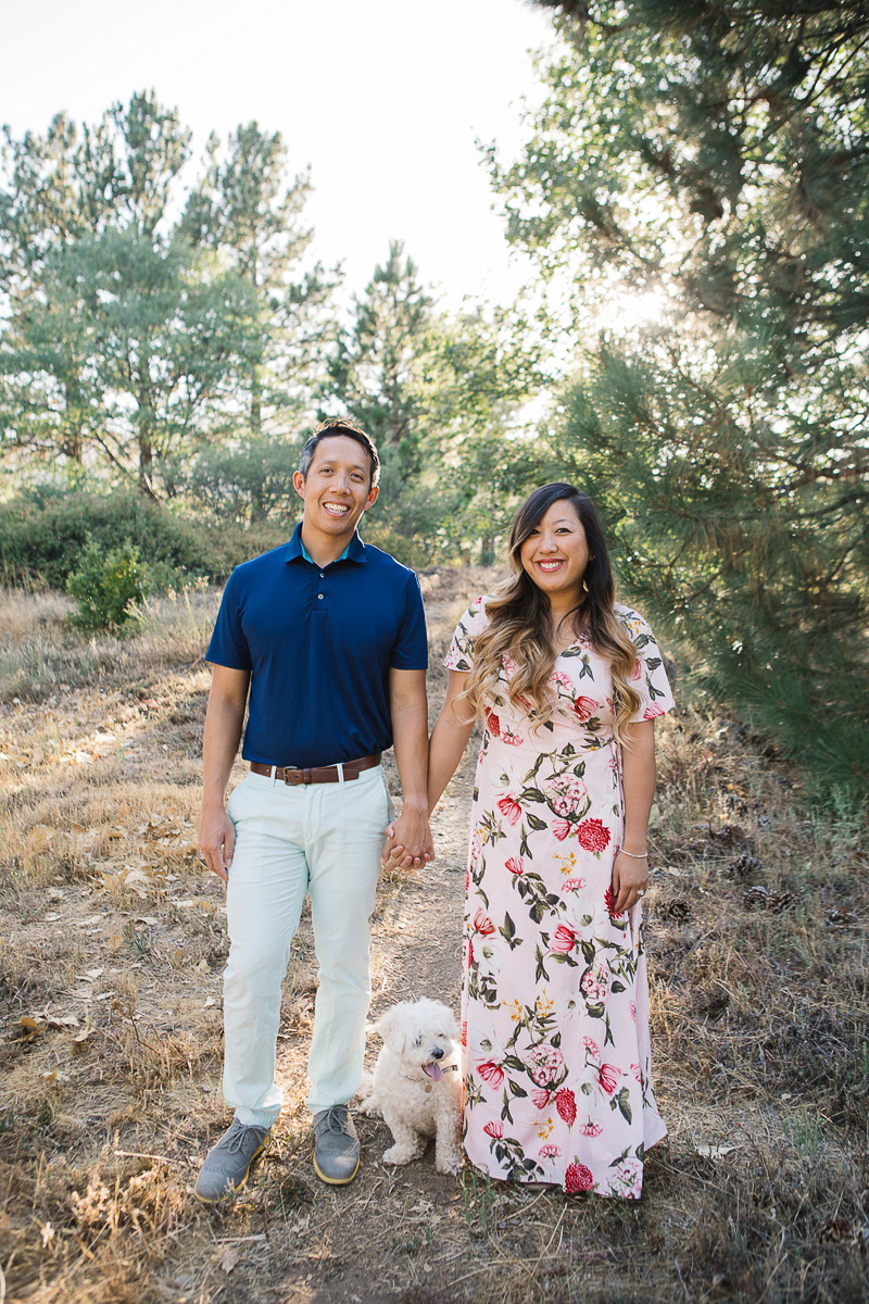 couple holding hands, dog standing between them, dog-friendly engagement photo ideas | ©Stephanie Fong Photography