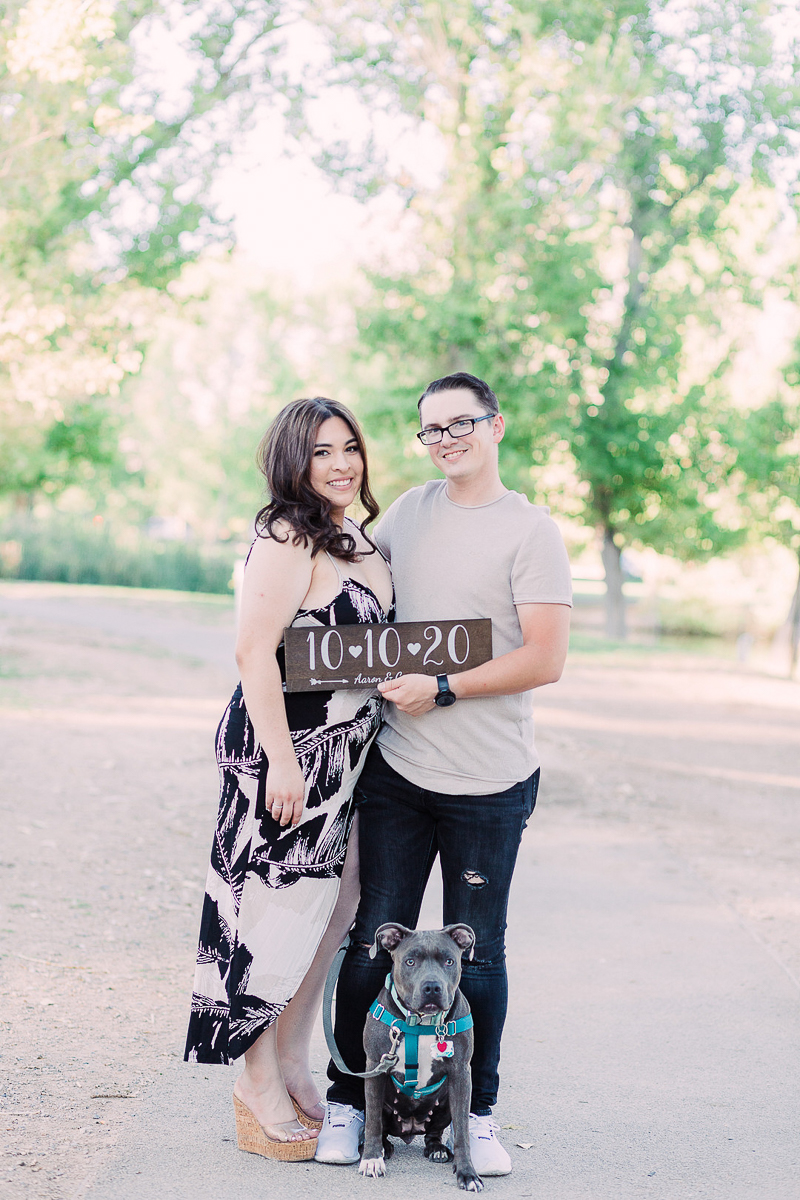 couple holding save the date sign, engagement photos with a pit bull | ©Fig + Willow Studios, Las Vegas, NV