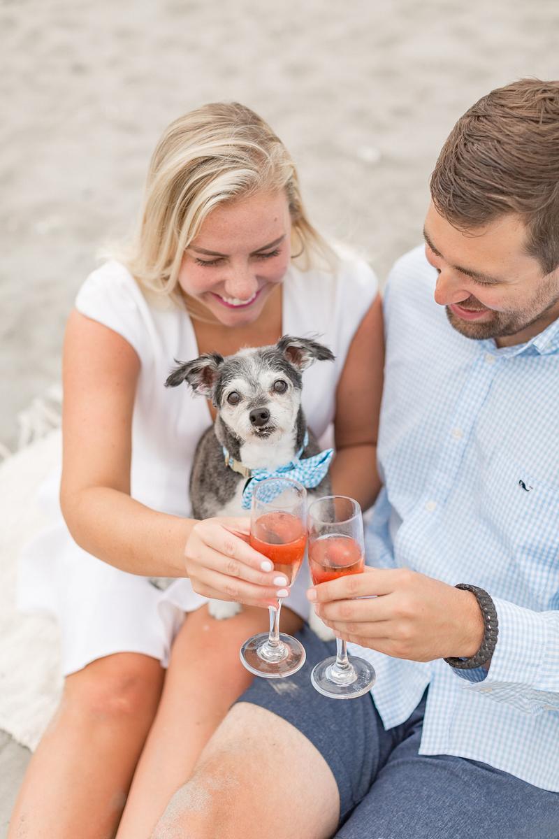 couple making a toast, dog-friendly engagement ideas, beach portraits | ©Coli Michael Photography