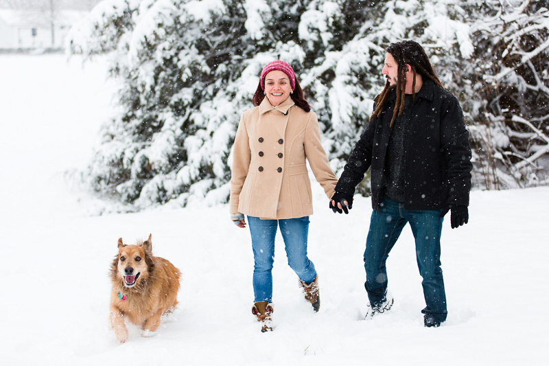 couple holding hands and walking through the snow with their Golden Retriever mix | ©Megan Rei Photography | Bealeton, VA