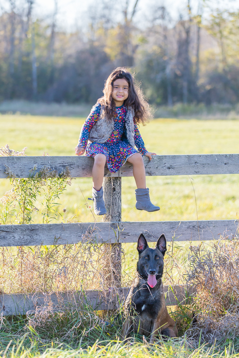 young girl sitting on fence with Malinois sitting below her, kids and dogs portrait ideas, ©Terri J Photography