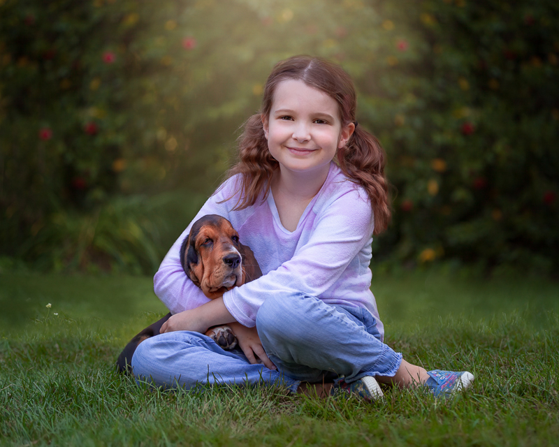 little girl with arms gently wrapped around puppy, kids and dogs portrait ideas | ©Terri J Photography