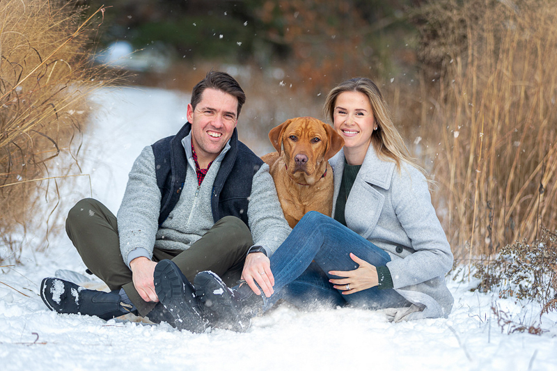 couple sitting on the snow with their Lab mix, dog-friendly family portraits, winter photography ideas | ©Terri J Photography, Toronto, Ontario