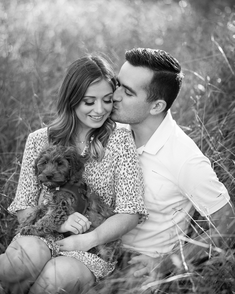 black and white timeless engagement portrait, couple in field with puppy | ©Celladora Photography + Video