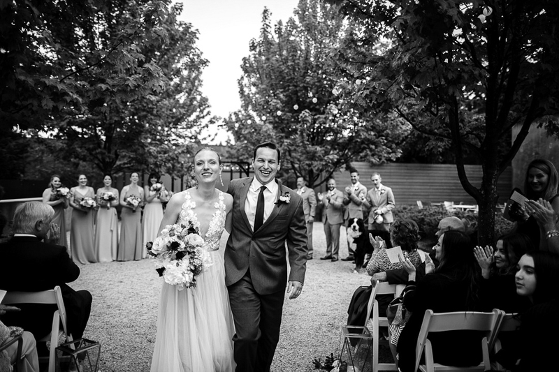 bride and groom, wedding party and dog in the background   ©J Tobiason Photography