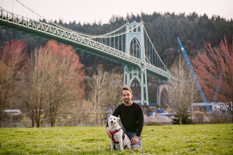 man kneeling next to Border Collie mix puppy with bridge in background, Cathedral Park   ©Kelly Carmody Photography