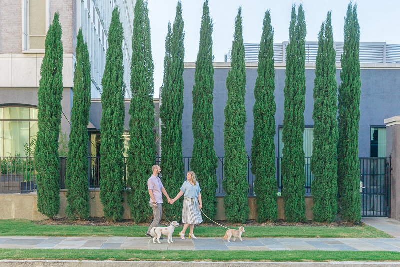 couple walking their dogs in front of tall evergreens, ©Charleston Photo Art, dog-friendly family portraits