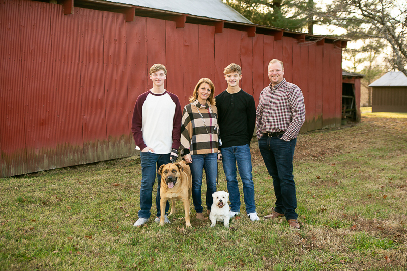 couple, teens, and dogs standing in front of red barn, dog-friendly family portraits | ©Mandy Whitley Photography