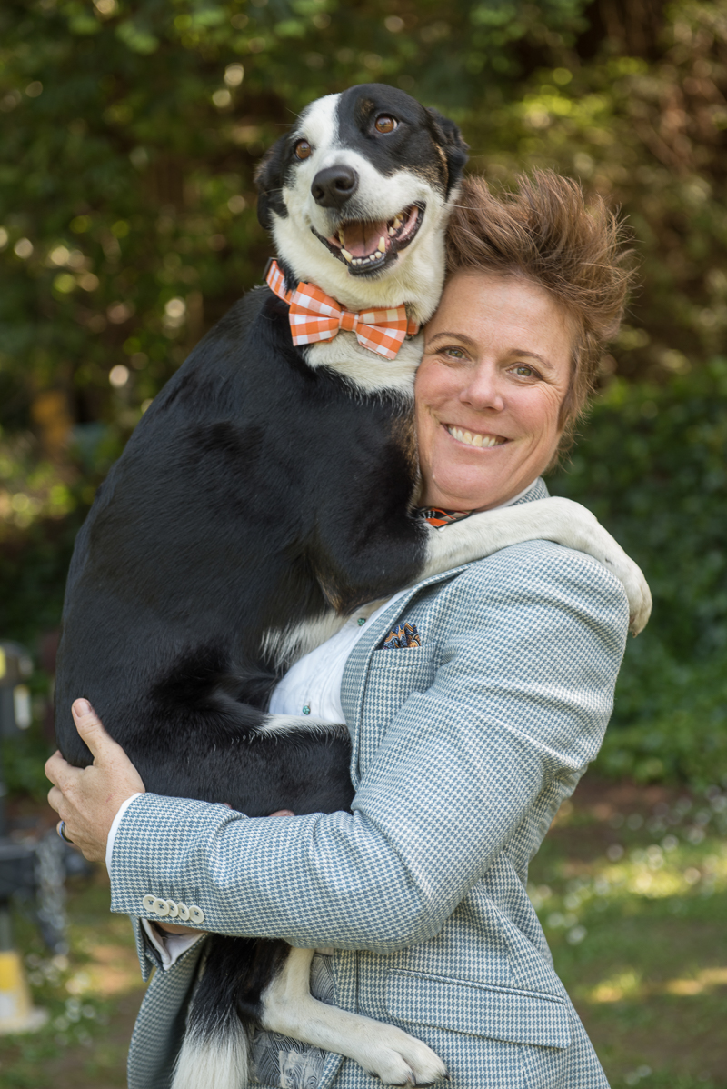 bride wearing suit holding black and white dog in orange gingham bow tie, Rustically Romantic Photography by Darby Johnson