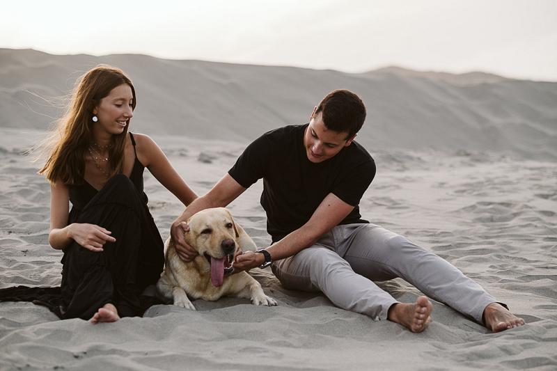 Labrador Retriever and couple sitting on the sand | ©Blancorazon Weddings
