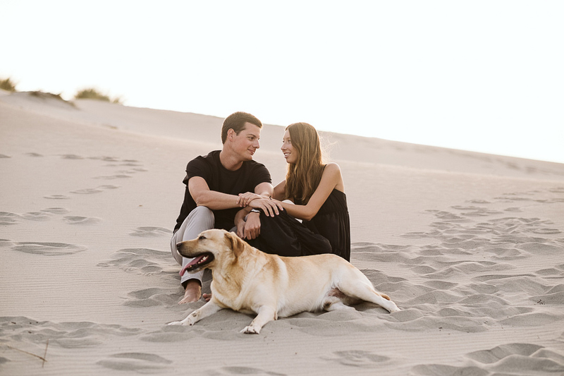couple sitting on dunes, Yellow Lab in front of them | ©Blancorazon Weddings