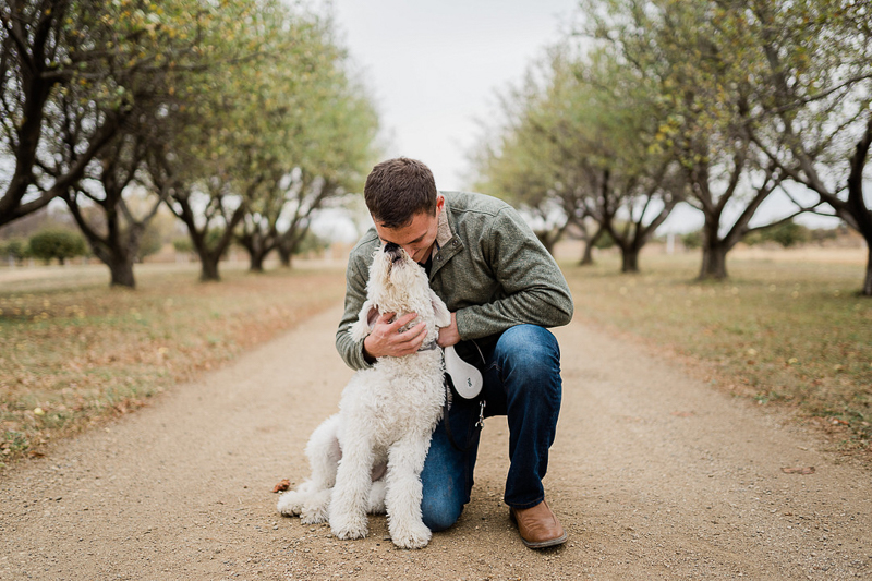 man hugging mini Goldendoodle dog, dog-friendly family photos, Sioux Falls, SD   ©Erica Jane Photography