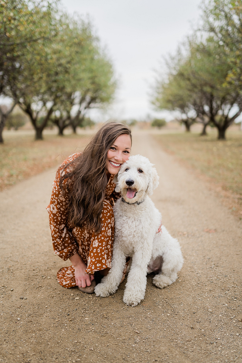 fall family photos with dog in orchard ©Erica Jane Photography